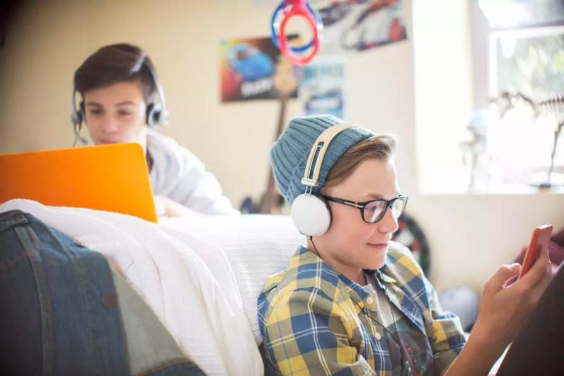 Two teenage boys using electronic devices in room