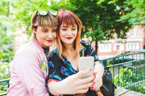 Two retro styled young women taking smartphone selfie in park