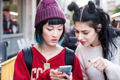 Two young stylish women looking at smartphone on city street