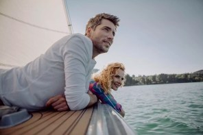 Smiling couple relaxing on a sailing boat