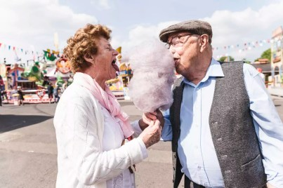 Senior couple on fair eating together cotton candy