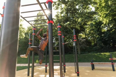 Muscular young man exercising on parcours bars