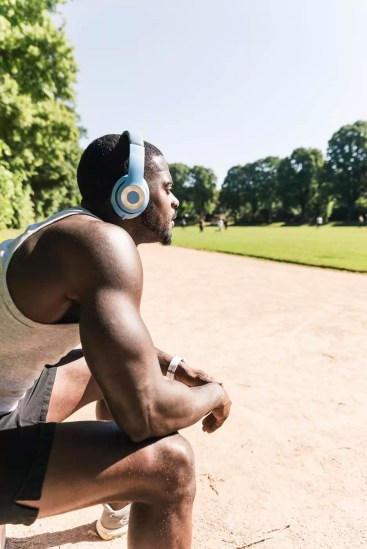 Smiling young athlete taking a break, wearing headphones, listening music