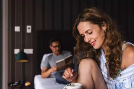 Smiling woman with cup of coffee in bedroom with man in background