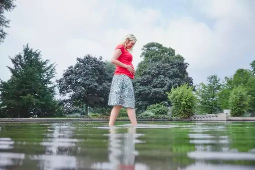 Pregnant woman walking through pond in park