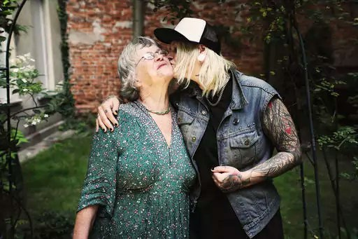 Daughter kissing mother while standing in back yard