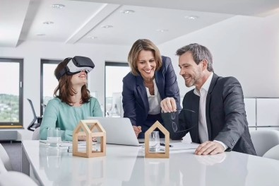 Business people having a meeting in office with VR glasses, laptop and architectural models