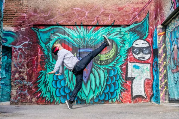 Young man with headphones dancing in font of graffiti