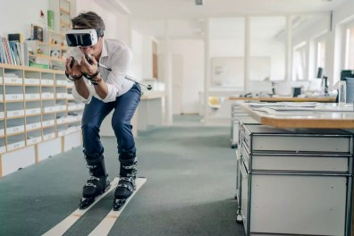 Businessman skiing in office, using VR glasses