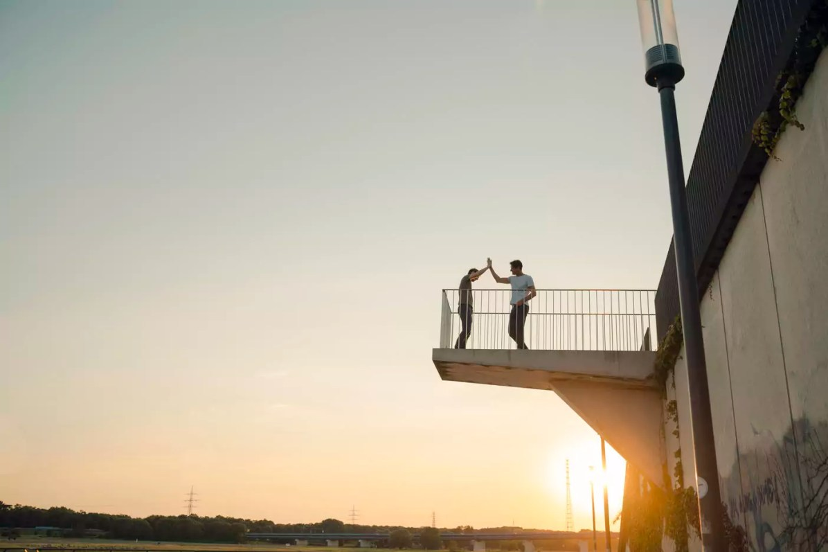 Two friends high-fiving at sunset, standing on observation platform