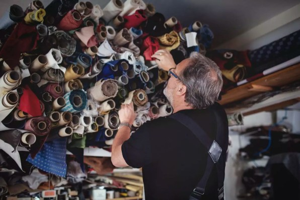 Low angle view of senior male owner looking at rolled fabrics in workshop