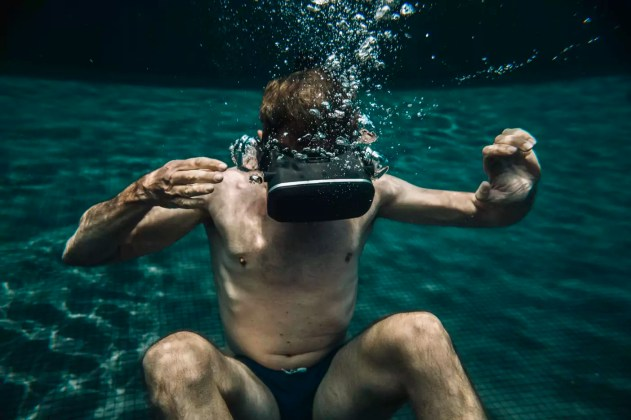 Man underwater in a swimming pool wearing VR glasses