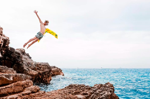 Man with airbed jumping from rock into the sea