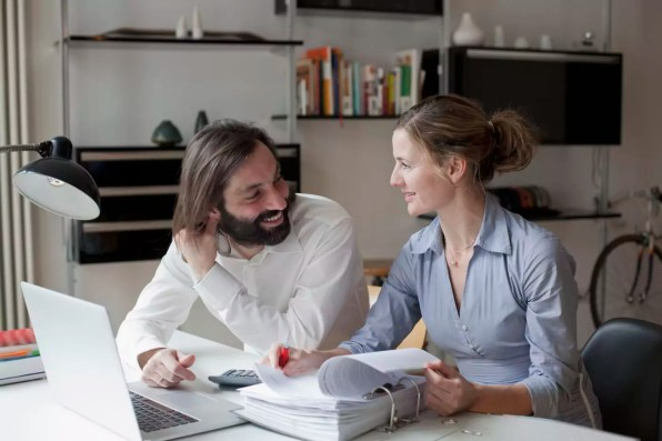 Mid adult couple looking at each other while working at home