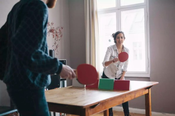 Young woman playing table tennis with man at home