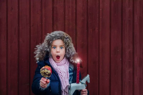 Girl standing in front of wooden wall with toy horse and chocolate dipped apple, looking amazed