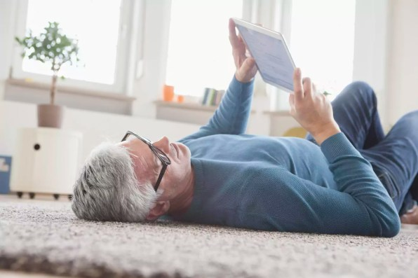 Mature man at home lying on floor using digital tablet