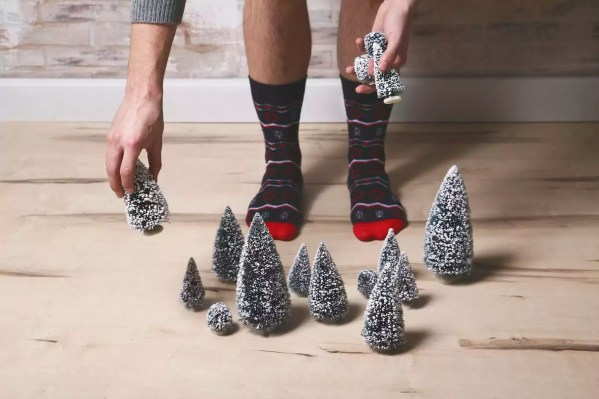 Young man wearing winter socks placing Christmas tree decoration on the floor
