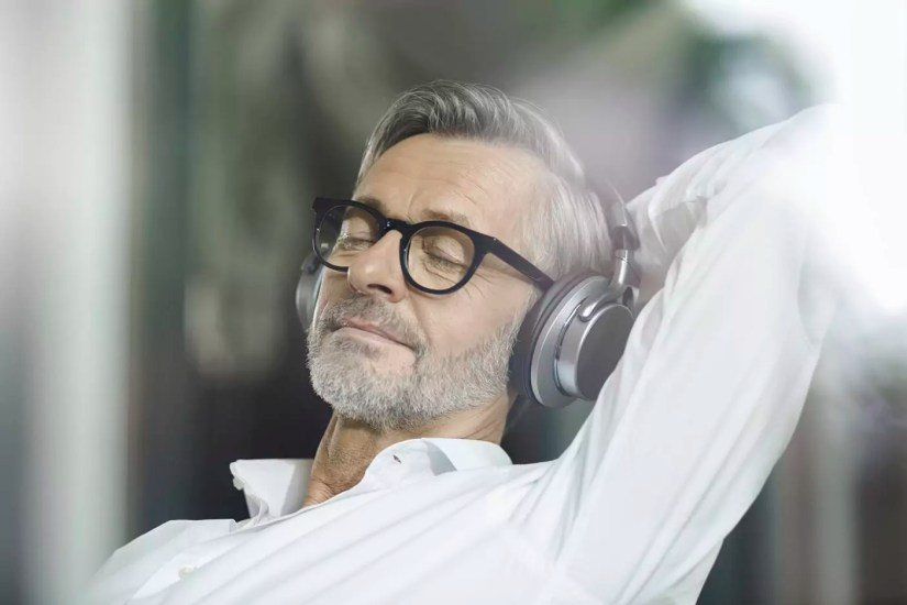 Portrait of man with eyes closed listening music with headphones