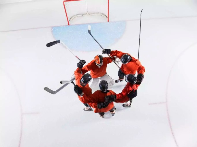 Overhead view hockey team in red uniforms huddling on ice