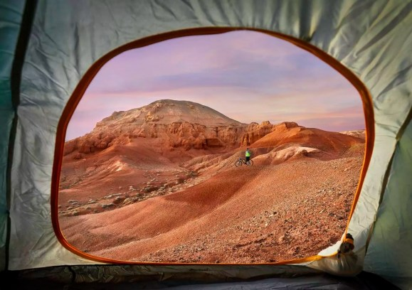 Mid distance view of hiker at desert seen through tent during sunset