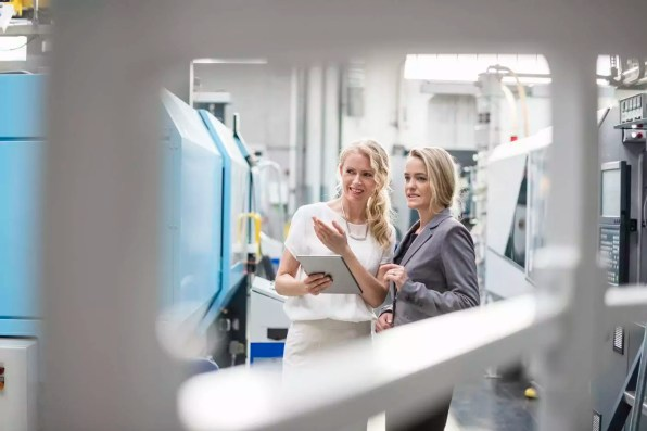 Two women with tablet talking in factory shop floor