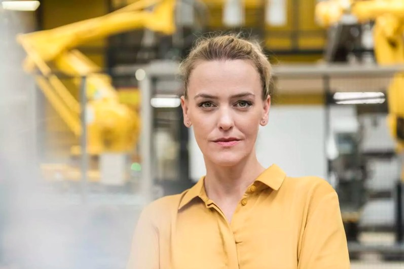 Portrait of confident woman in factory shop floor with industrial robot