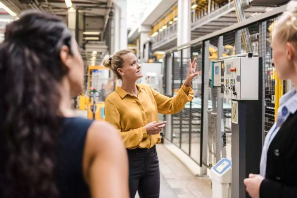 Woman explaining machine to colleagues in modern factory