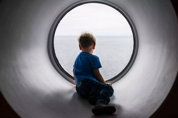 Back view of boy looking through window at Baltic Sea