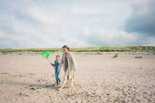 Mother and daughter walking to the sea with a dip net