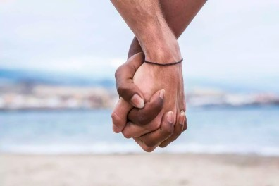 Close-up of two hands connected on the beach