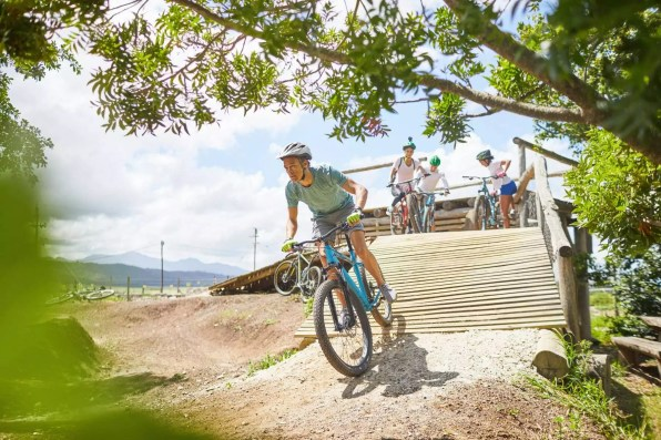 Man mountain biking down sunny obstacle course ramp