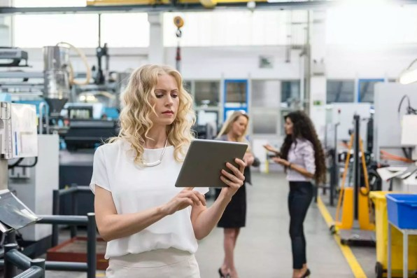 Woman using tablet in factory shop floor with two women in background