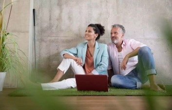Casual businessman and businesswoman sitting on artificial turf in a loft sharing laptop