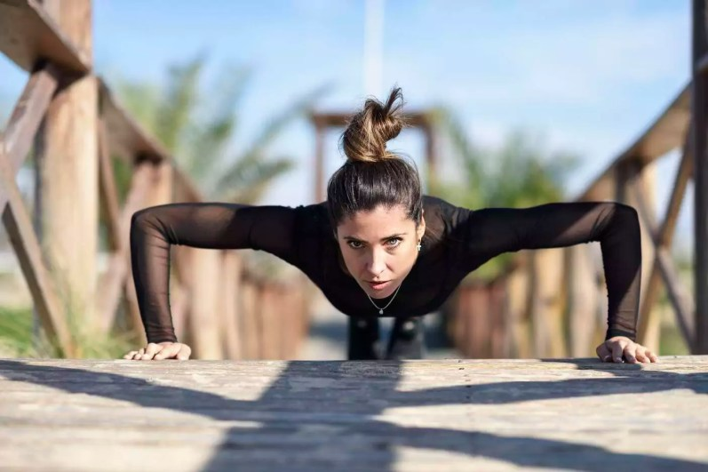 Spain, Andalusia, Cadiz. Middle-aged woman with fit body doing push-ups on a wooden bridge on the beach. Sports and fitness concept.