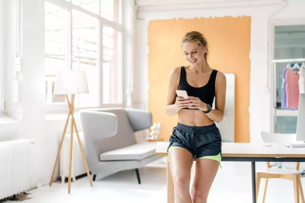 Smiling young woman in sportswear looking at cell phone