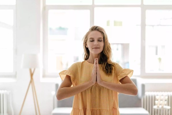 Young woman wearing a dress practising yoga