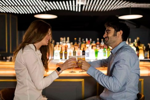 Smiling couple clinking beer glasses in a bar