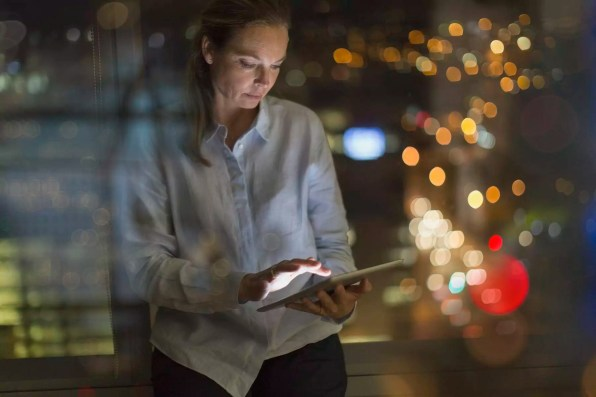 Businesswoman working late at digital tablet in office at night