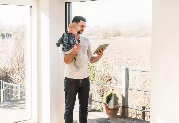 Father standing at home, carrying baby son and reading text messages