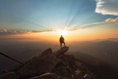Man standing on rock at cliff against sky during sunset