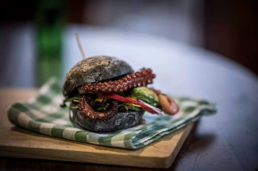 Black burger with fried octopus and vegetables