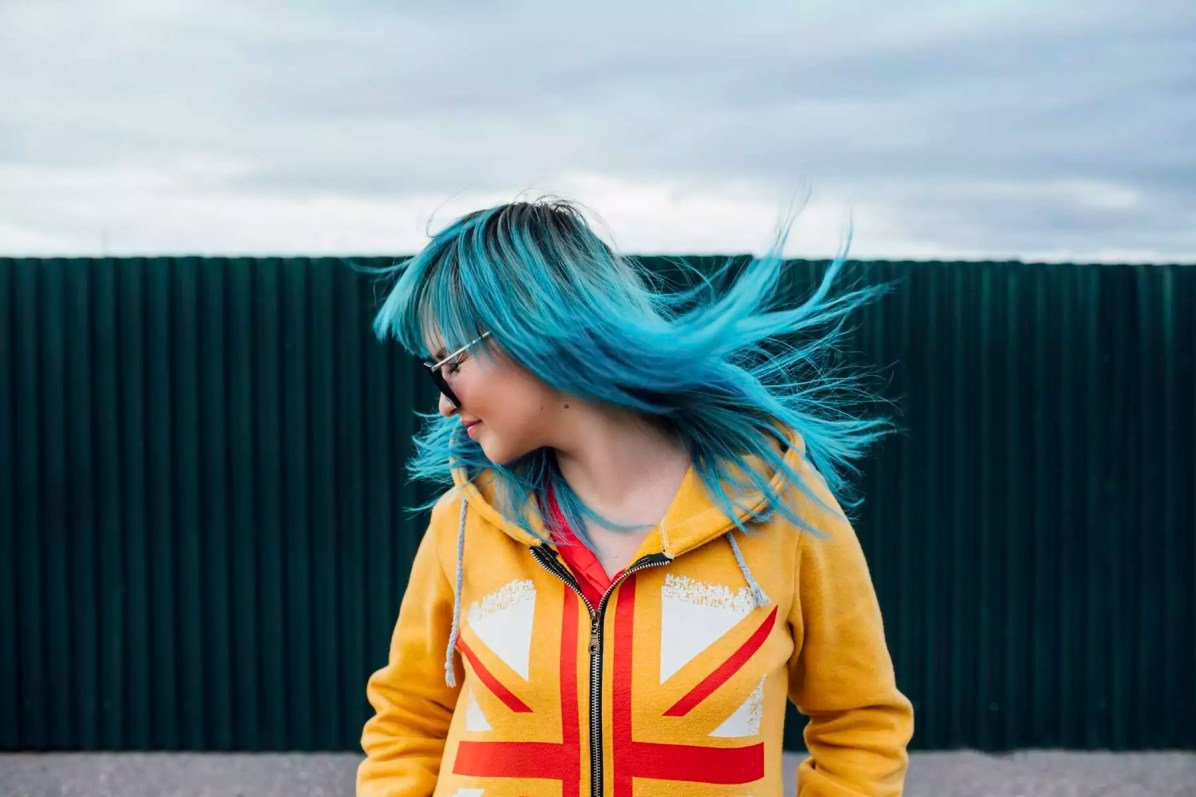 Young woman with blowing dyed blue hair