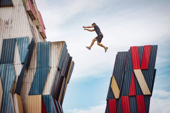 Low angle view of man jumping over buildings against sky
