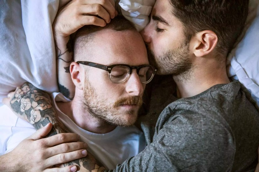 High angle close-up of loving homosexual couple lying on bed at home