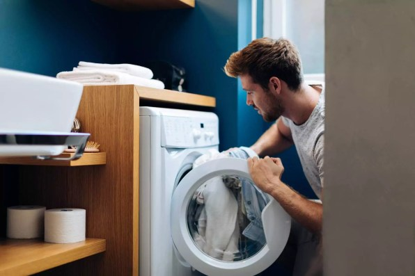 Young man putting laundry into washing machine at home