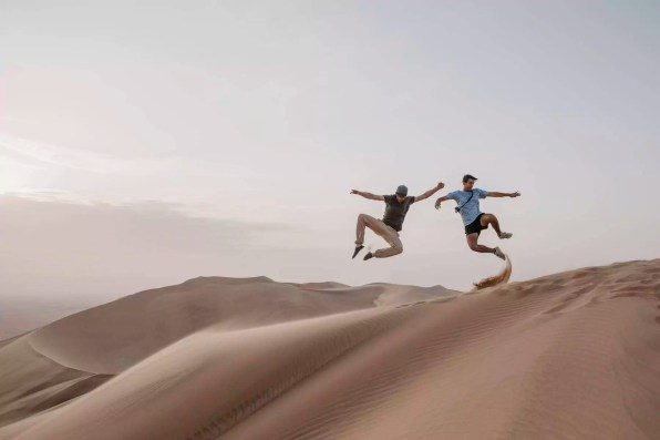 Namibia, Namib, two friends jumping in the air on desert dune