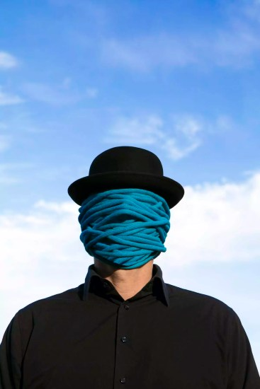 Man wearing bowler hat with rope wrapped around his face