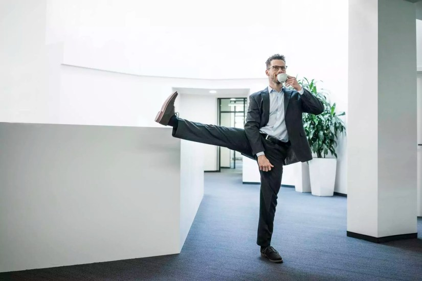 Businessman with cup of coffee standing on one leg in office