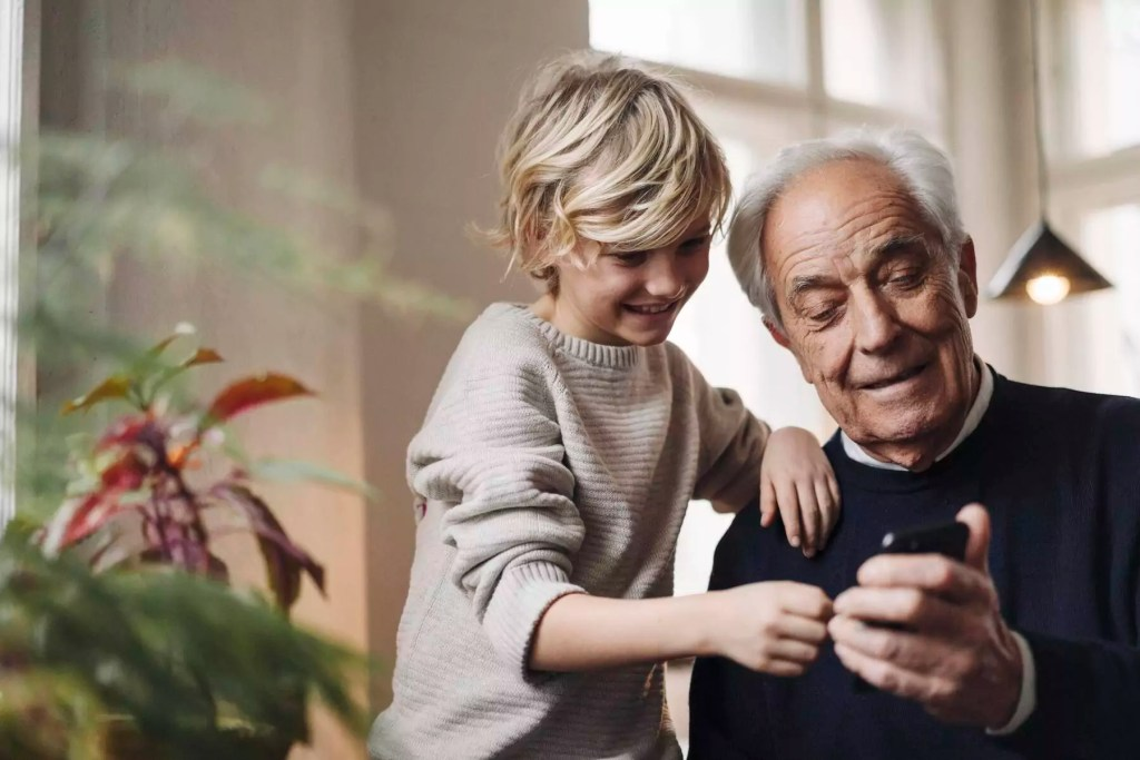 Happy grandfather and grandson using cell phone at home - GUSF02161